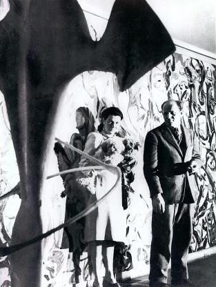 """Peggy Guggenheim y Jackson Pollock delante de """"Mural"""" (1943) en la entrada de la casa de la coleccionista. Fuente: Iowa.edu"""