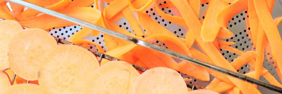 Fijn geschaafde wortel en zoete aardappel op inox rek voor groentechips.