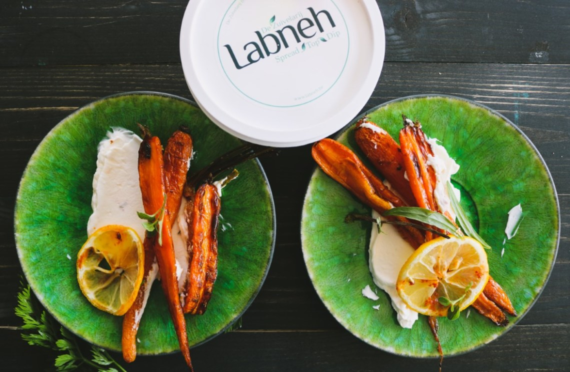 Labneh with roasted carrots, lemon slices and harissa oil.