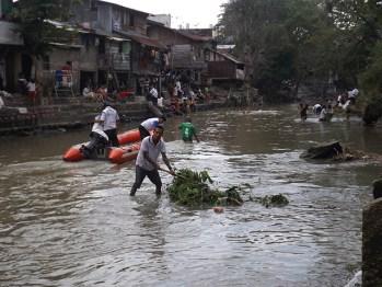 Seorang warga memindahkan ranting-ranting pohon dari sungai.