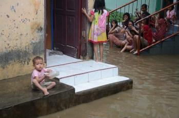 Seorang anak duduk di depan rumahnya. Tak jauh darinya, sekelompok remaja duduk-duduk di tangga dengan kaki terrendam banjir.