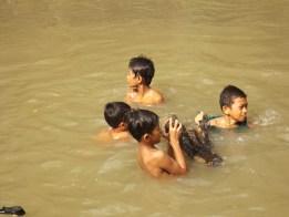 Anak-anak mengangkat kayu dari sungai.