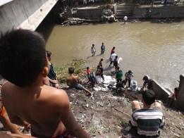 Warga bahu membahu mengangkat sampah dari bawah jembatan menggunakan goni dan tali.