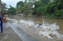 Debur air Sungai Deli ketika sekelompok anak-anak melompat bersamaan
