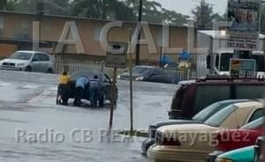 Un conductor que se aventuró a cruzar la inundación, terminó empujando su carro con la ayuda de otras personas (Foto Radio CB REACT Mayagüez)