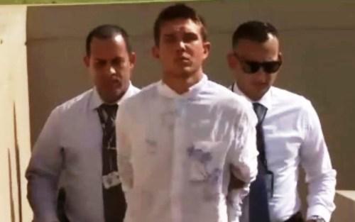 Justin Acosta McGowan es escoltado por agentes de la División de Homicidios del CIC de Mayagüez (Captura de pantalla Noticentro).