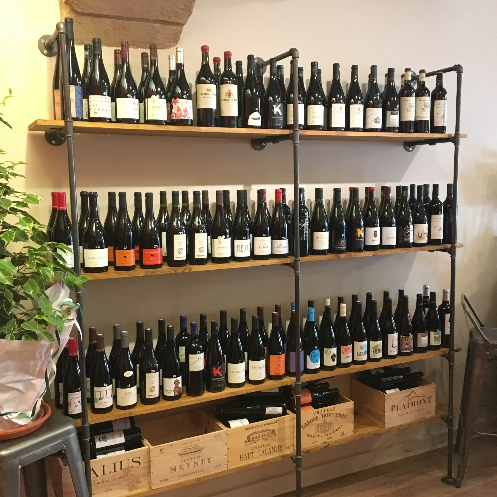 Cave à vin - Our selection of red natural, organic a,d biodynamic wines on hand built cast iron and oak shelves with wooden wine boxes.
