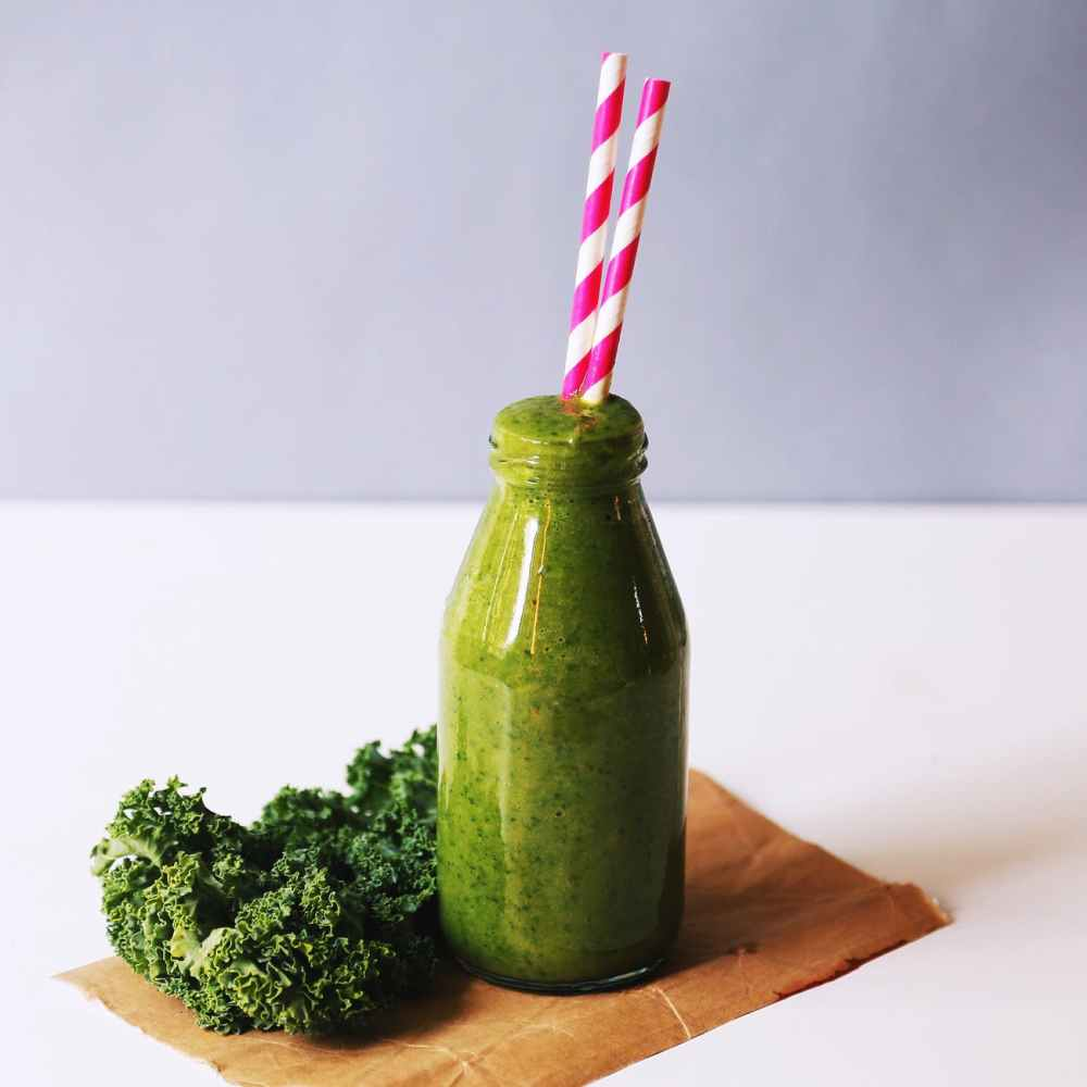 clear glass bottle filled with broccoli shake