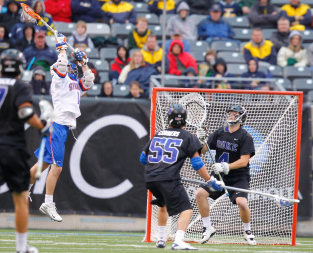 Apr 1, 2012; East Rutherford, NJ, USA; Syracuse Orange attack Tommy Palasek (14) shoots on goal and scores against Duke Blue Devils goalie Dan Wigrizer (4) at the Big City Classic at MetLife Stadium. Mandatory Credit: Jim O'Connor-USA TODAY Sports
