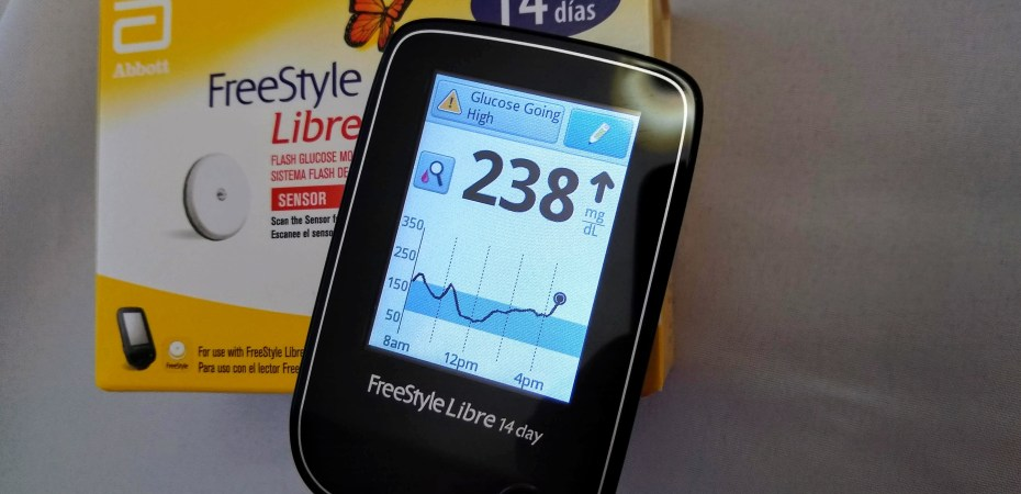 The Libre Reader is showing a High Glucose warning and an up trend arrow