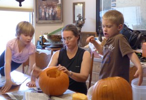 Tiarnan prepares to attack his pumpkin (with a little help from Maeve and Meghan)