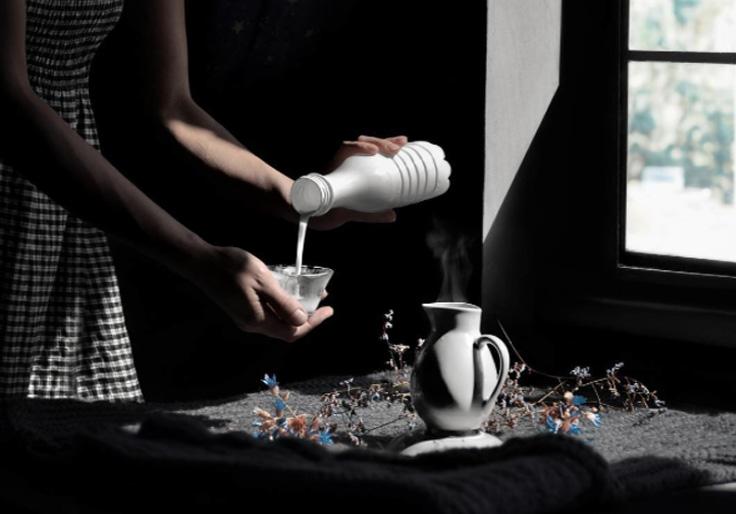 femme versant du lait sur fond noir
