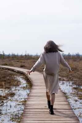 woman walking on wooden path in windy weather in spring