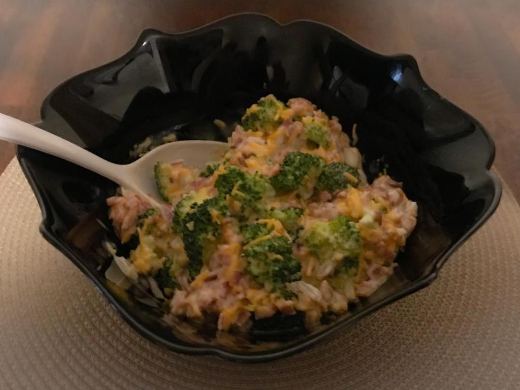 Best ever creamy crunchy broccoli salad recipe containing broccoli florets, crumbled bacon, chopped red onion, shredded cheddar cheese, mayo, white vinegar, and sugar.