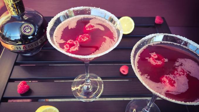Raspberry Bliss Martini made with Raspberry Vodka, Chambord, Cointreau, Lemon Juice, Sweet 'n Sour, and garnished with a sugar rim and fresh raspberries