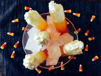 Candy corn shots made with candy corn, cake vodka, pineapple juice, and whip cream.