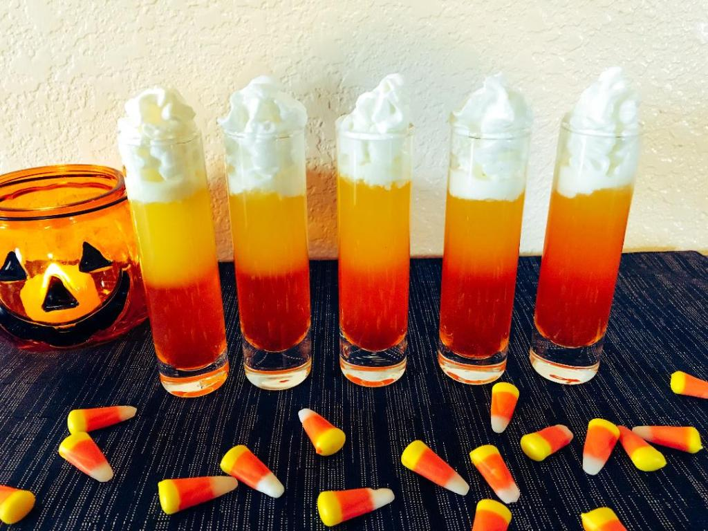 Candy corn shots made with Pinnacle Cake Vodka, candy corn, pineapple juice, and whip cream
