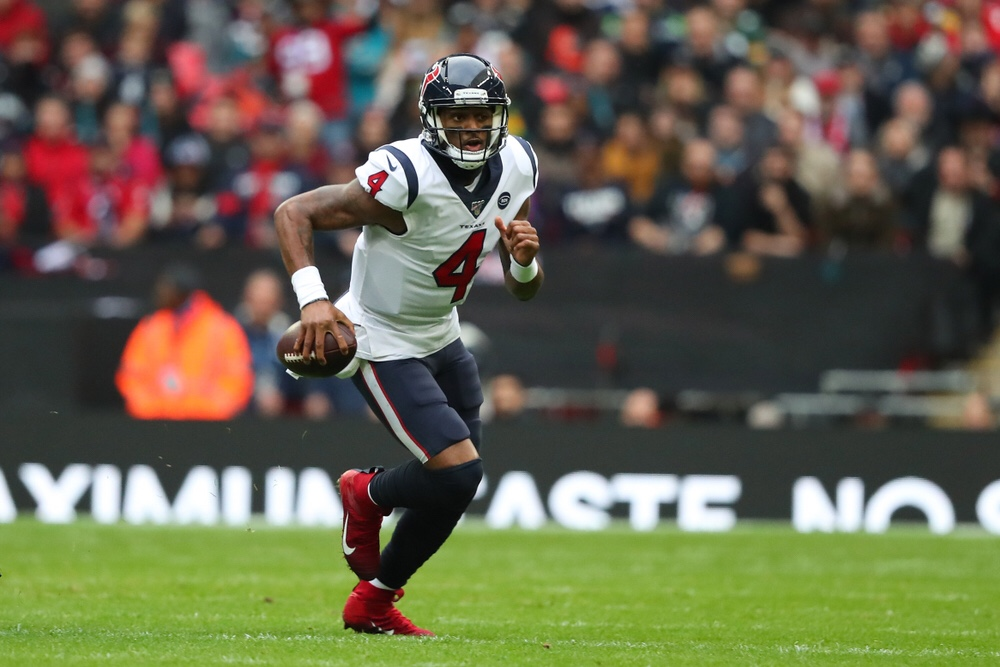 NFL Houston Texans quarterback Deshaun Watson running with the football in one hand.