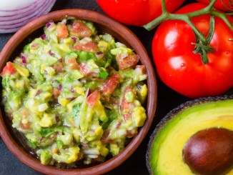 Green Chile & Tequila Guacamole in a bowl with tomatoes and avocado ingredients surrounding the serving bowl