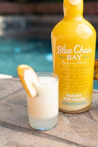 A bottle of Banana Rum Cream an a shot of Banana Rum Cream sitting next to the pool.