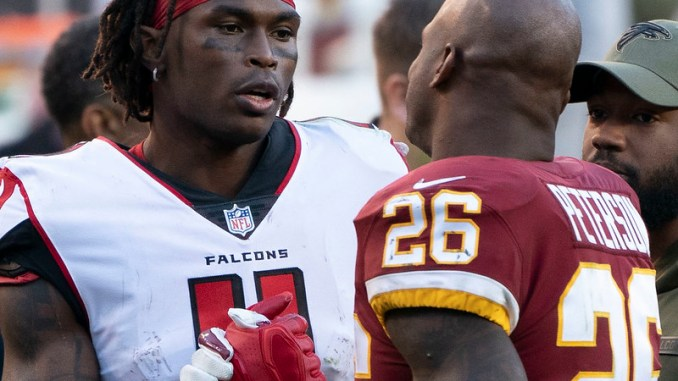 NFL players Atlanta Falcons wide receiver Julio Jones shaking hands with Washington running back Adrian Peterson