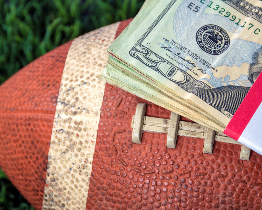 A football laying in the grass with a stack of $20 bills on top of it