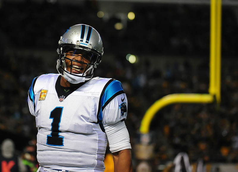 NFL quarterback Cam Newton smiling after a game.