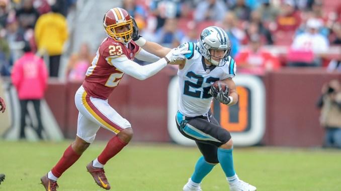 NFL Carolina Panthers running back Christian McCaffrey stiff arming a Washington Football Team defender in a football game.