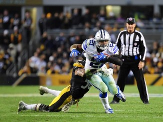 NFL Dallas Cowboys running back Ezekial Elliott running with the football and dragging a Pittsburgh Steelers defender trying to take him down with him