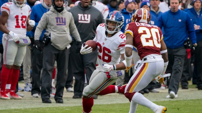 NFL New York Giants running back Saquon Barkley running with a football for a touchdown against the Washington Football Team