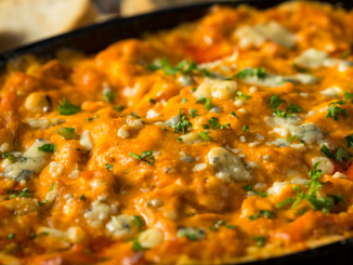 Baked Buffalo Chicken Dip in a black cast iron skillet served with French bread slices
