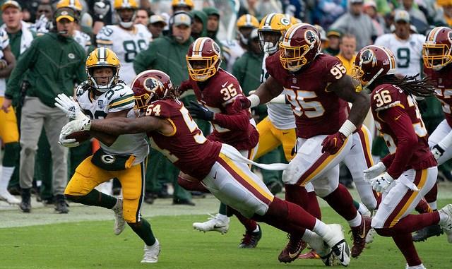 NFL Green Bay Packers running back Aaron Jones avoiding a tackle against a Washington Football Team defender