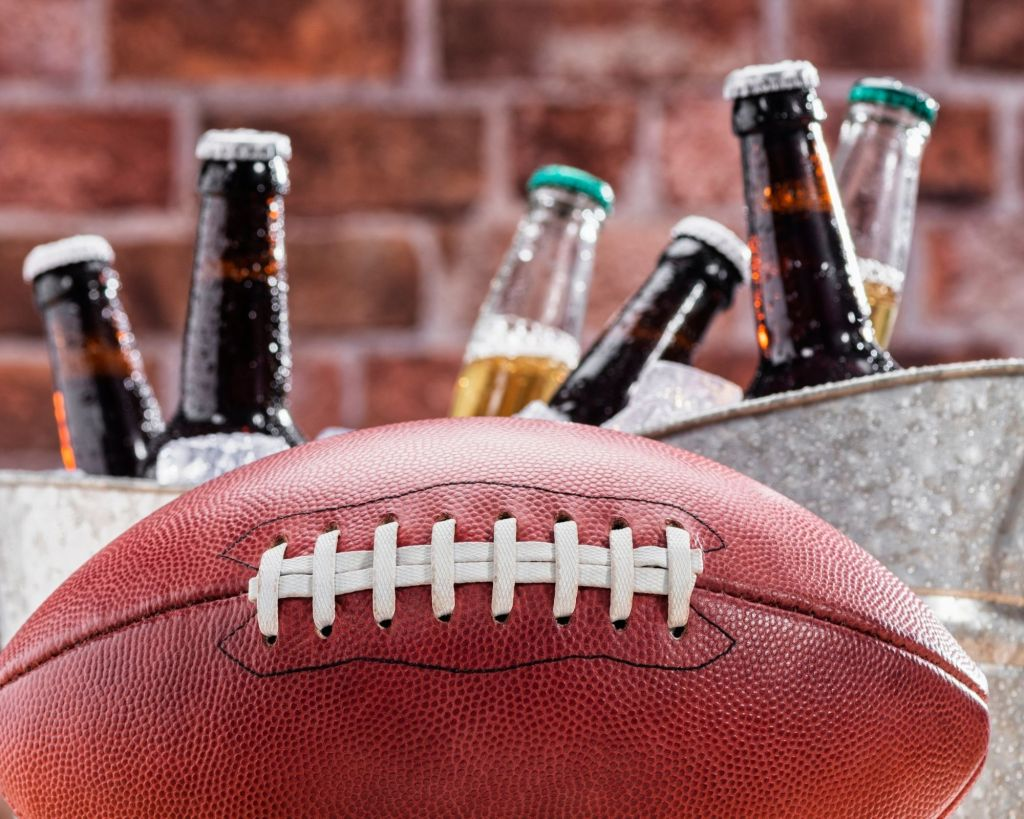 A big silver beer tub stocked with ice and bottled beers. An American leather football sitting in front of the beer tub.