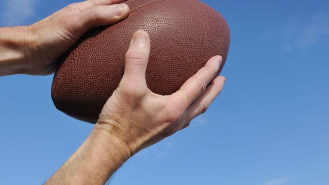 A person holding a football pointed up into the blue sky.