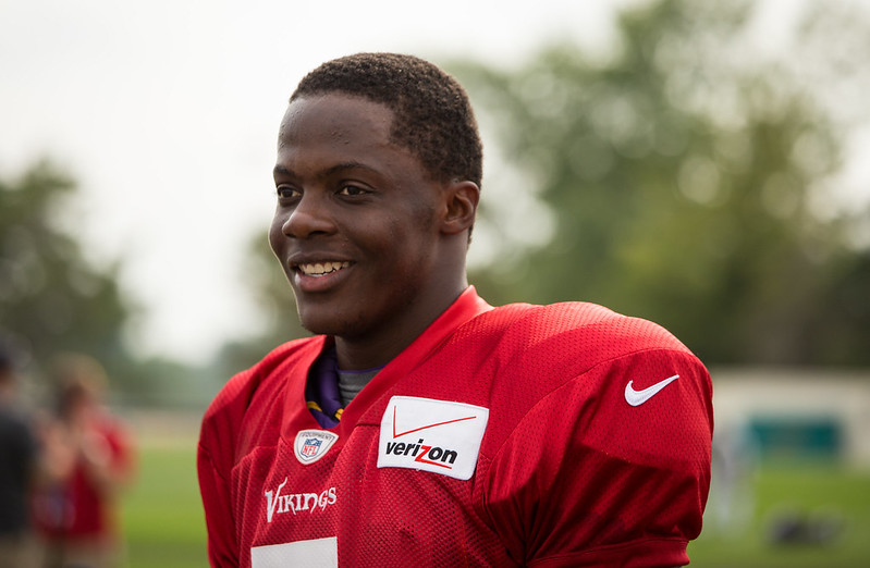 NFL quarterback Teddy Bridgewater smiling during football practice and wearing a red non-contact jersey