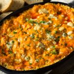 Baked Buffalo Chicken Dip in a black cast iron skillet right out of the oven, and served with French bread slices.