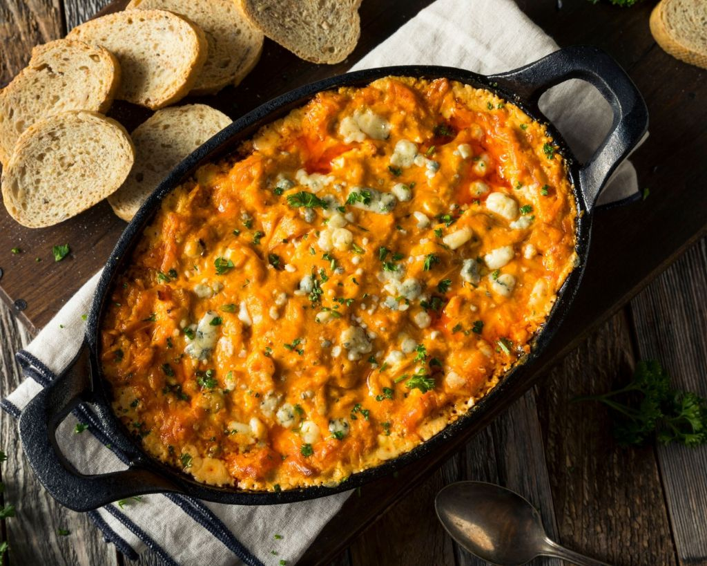 Baked Buffalo Chicken Dip in a cast iron skillet. The skillet is sitting on a towel and dark brown wooden cutting board. The dip is served with French bread slices sitting around the skillet.