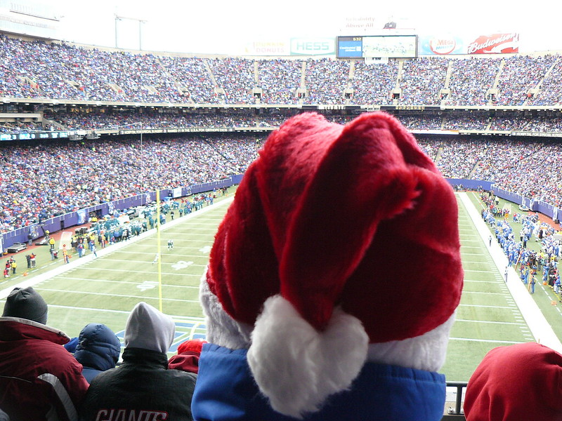 Football fan at a New York Giants football game sitting in the stands with a santa hat on.