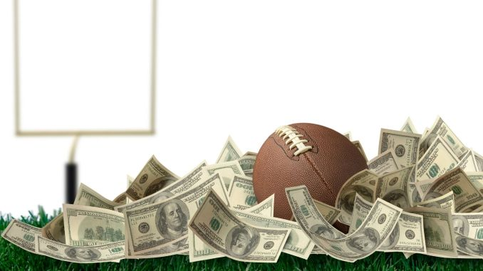 A football sitting in a pile of money in front of a goal post
