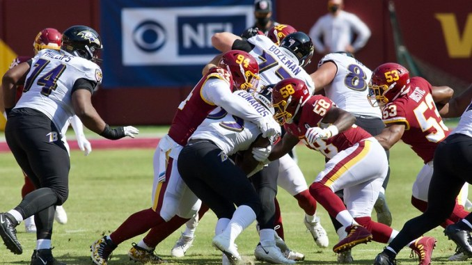 Baltimore Ravens running back Gus Edwards getting tackled by a Washington Football Team defender
