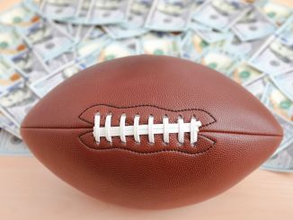 A football sitting in front of a pile of $100