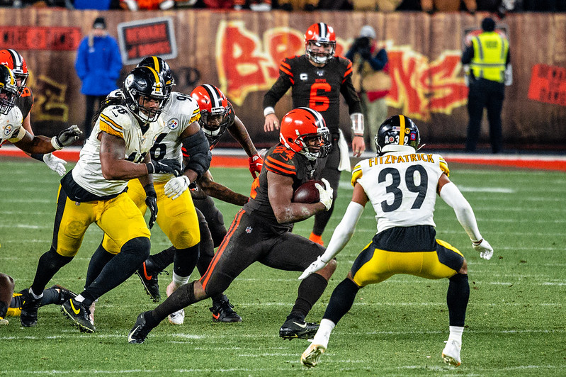 NFL running back Nick Chubb avoiding a tackle against the Pittsburgh Steelers defense.