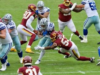 NFL Dallas Cowboys running back Tony Pollard avoiding a tackle from a Washington Football Team defender.