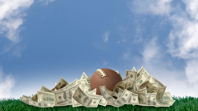 A football sitting on a pile of money outside.