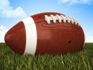 A football sitting outside on grass with a blue sky in the background.