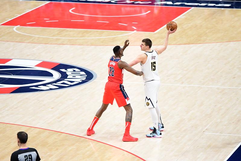 NBA Denver Nuggets center Nikola Jokic playing keep away against a Washington Wizards defender.