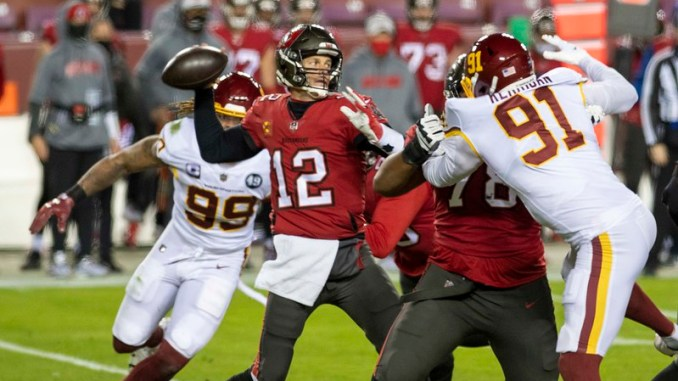Tampa Bay Buccaneers quarterback getting ready to throw a pass against Chase Young and the Washington Football team defense in the Wild Card Round of the 2021 playoffs.