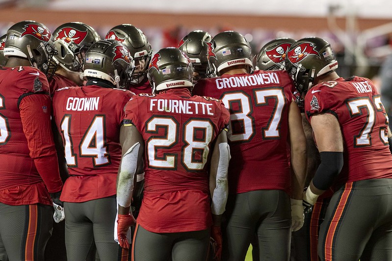 The Tampa Bay Buccaneers offense in a huddle on the football field.