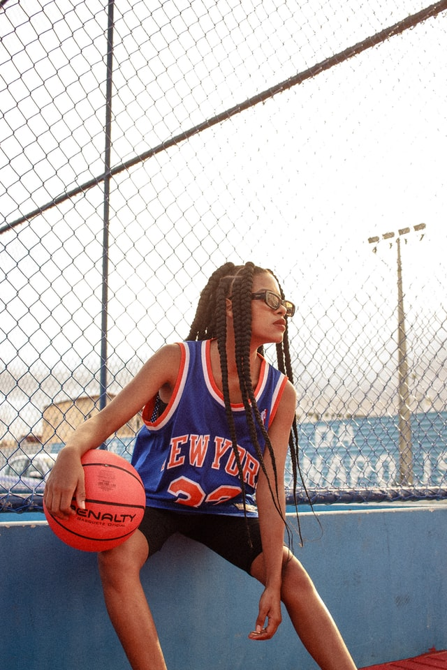 A woman wearing a New York Knicks jersey and holding a basketball under one arm.