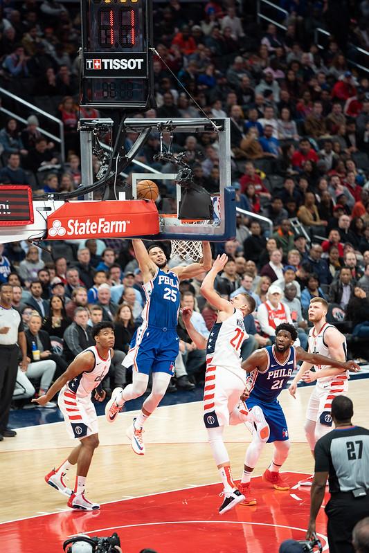 NBA Philadelphia 76ers Ben Simmons dunking the basketball on Washington Wizards defenders.